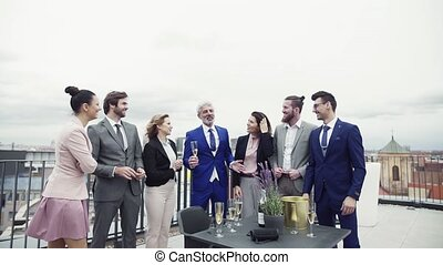 A group of joyful businesspeople having a party outdoors on...