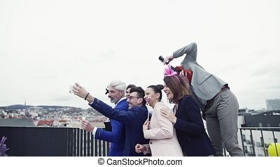 A group of joyful businesspeople outdoors on roof terrace in...