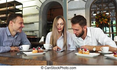 A group of men and women in office clothes are sitting in a cafe at a big table and discuss the past working day