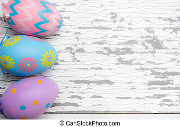 A group of pastel colored Easter eggs on a white wooden background