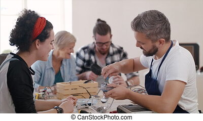 A group of people at repair cafe repairing household electrical devices.