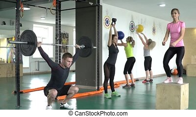 A group of people doing sports exercises in the gym.
