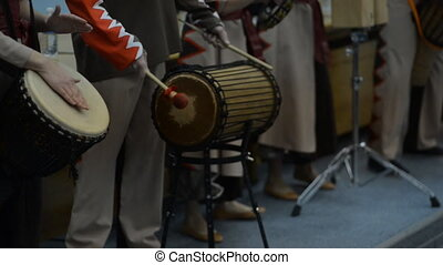 A group of people in costumes playing the African drums