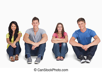 A group of people sitting on the ground together with knees up