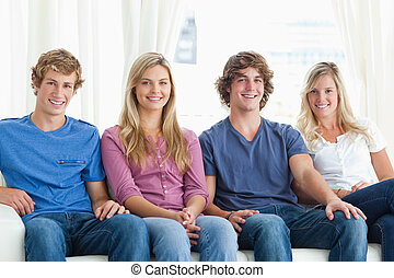 A group of people sitting together on the couch