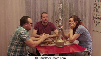 A group of people smoking shisha and playing cards
