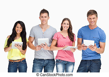 A group of people standing with their tablets in their hands