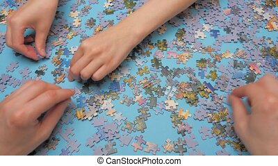A group of puzzles, hands on a blue surface background. Puzzle game, Preschool education. Family pastime concept. Engaging in successful work.