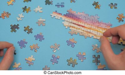 Assembling jigsaw puzzle. Pieces of a jigsaw puzzle for entertainment when you have to stay home during a lock down. Part of the whole. Family activity. Assigning to learn a segment. Pastime background