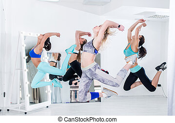 A group of slim fit athletic young women doing simultaneous...