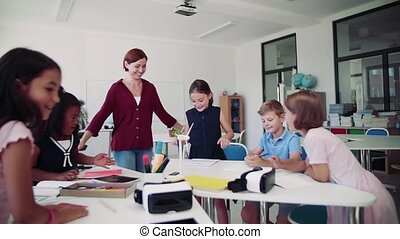 A group of small school kids with teacher in class learning ...
