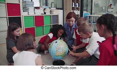 A group of small school kids with teacher sitting on the ...