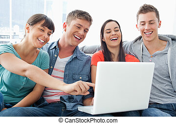 A group of smiling friends gathered around a laptop