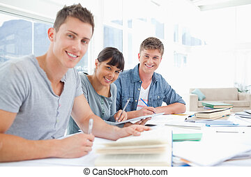 A group of smiling students look into the camera as they all do homework