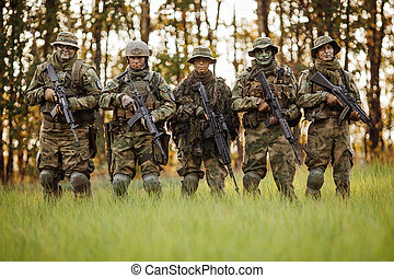 a group of soldiers standing in the woods and looking forward