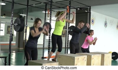 A group of sports people in the gym jump on wooden boxes....
