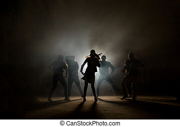 a group of street dancers performing different moves on the dark street