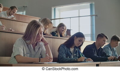 A group of students listening to a lecture at the University from a Professor. Large audience for College lectures.
