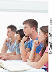 A group of students sitting in class listening