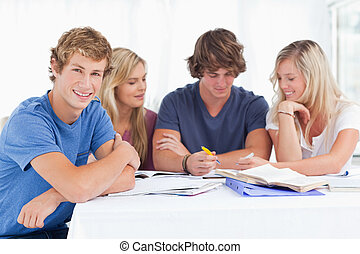 A group of students sitting together as they all study as one smiles while looking at the camera