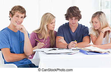 A group of students sitting together as they all study as one smiles and looks at the camera