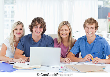 A group of students with a laptop look into the camera
