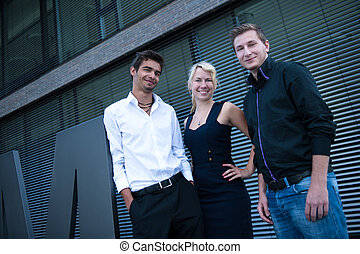 a group of three business people standing together