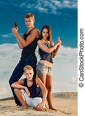 A group of three teenagers on the beach purposeful looks. The sk