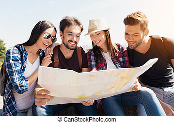 A group of tourists are sitting in a park on a bench. They together look at the world map, and decide where to go next.