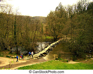 A group of tourists hiking, cross the ancient Tarr Steps Bridge.