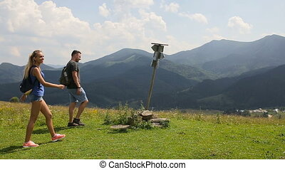 A group of tourists looking for a road in the mountains with a pointer and phone