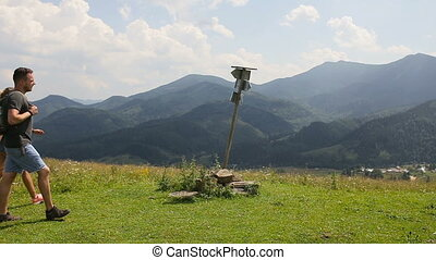 A group of tourists passes by a signpost in the mountains