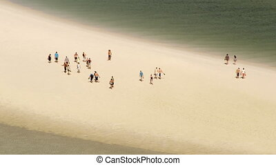 A group of tourists walking on white sand