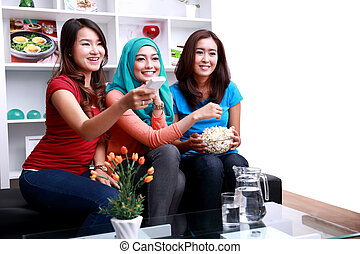 a group of women enjoy watching a movie