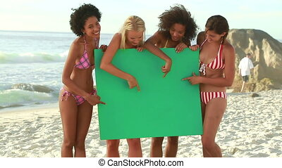 A group of women holding a green screen
