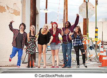 A group of young angry punk rock teens shout across the street.