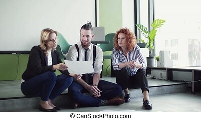 A group of young business people sitting on the floor in an office, talking.