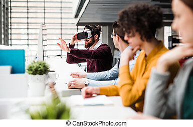 A group of young businesspeople with VR goggles working in office.