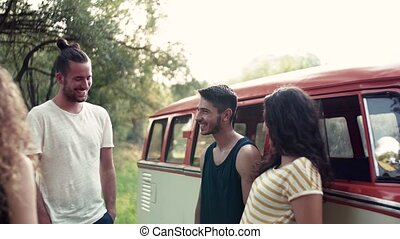 A group of young friends on a roadtrip through countryside,...