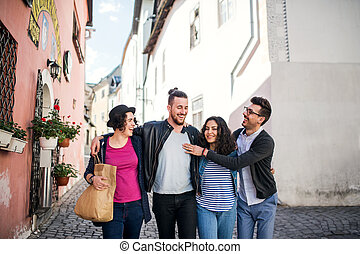 A group of young friends walking outdoor in town, talking.