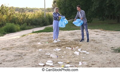 A group of young people enjoy voluntary garbage collection on the beach.