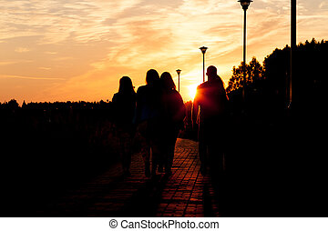 A group of young people walking to sunset in city park