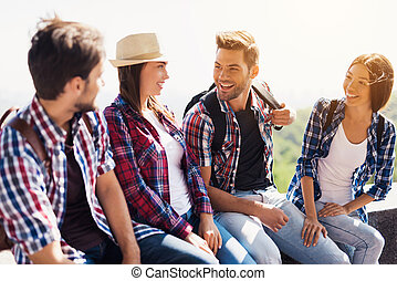 A group of young tourists sitting on a bench in the park and talking. They smile happily and look at each other.