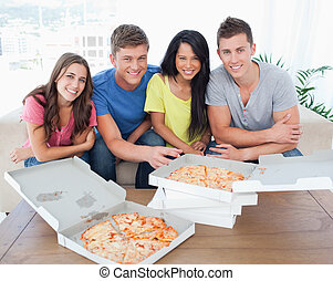 A group sitting in front of delicious pizza as they look into the camera