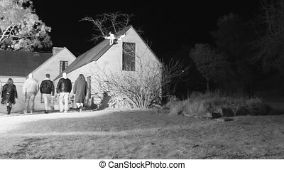 A group walking towards a haunted house - A steady shot of a...