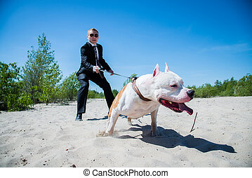 A guard in a business suit with a combat dog on a leash