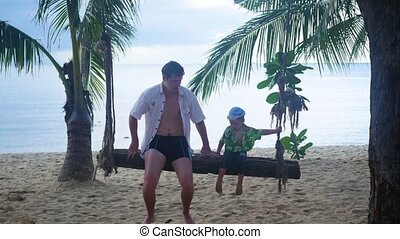 a guy and a child swinging on a rope swing on the beach