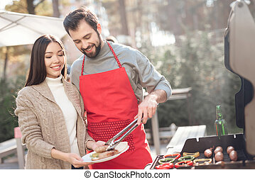 A guy and a girl are cooking barbecue food during a picnic with friends.