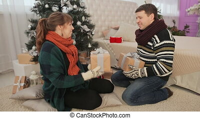 A guy and a girl are exchanging Christmas presents and hugging each other