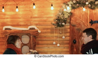 A guy and a girl throw artificial snow against the backdrop of a fairy-tale house. Christmas and New Year theme